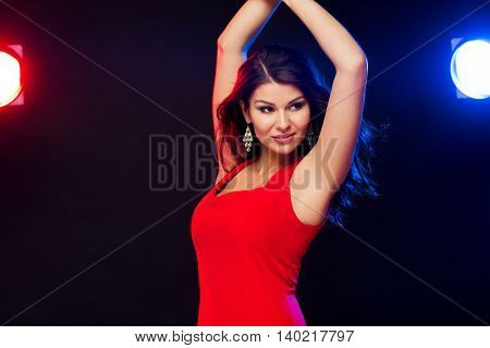 people, holidays, disco, night lifestyle and leisure concept - beautiful sexy woman in red dress dancing at nightclub