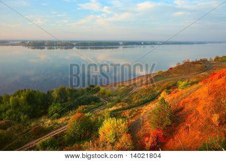 Big river Kama in sunrise light with autumn trees on a coast.