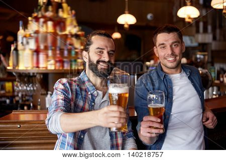 people, men, leisure, friendship and party concept - happy male friends drinking draft beer at bar or pub