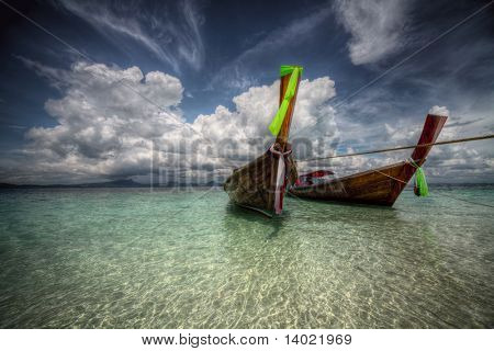 Old traditional long tail boats near a sand coast in clear transparent water