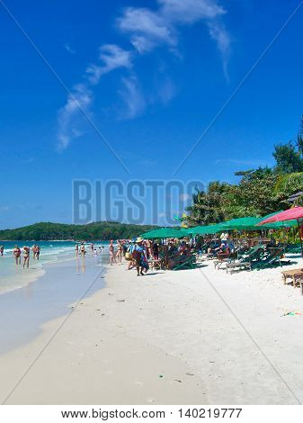 beautiful beach with idyllic beach chairs and sunshades. Tourist walking along the beach and swimming in the turquoise water.
