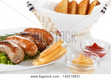 Roast beef or chicken sausage on a plate with ketchup mustard and rosemary.