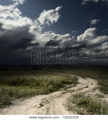 Rural road in field with wild herbs and dark storm clouds