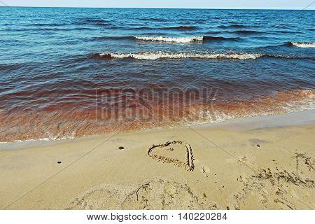 Heart on sand behind blue Baltic sea