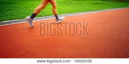 Motion blurred sportsmen running on red stadium's track