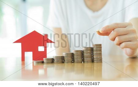 Real estate investment. House and coins on table.