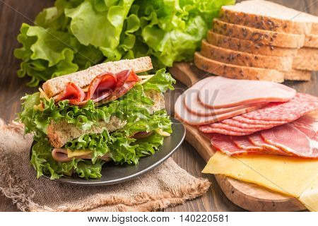 Club sandwich on a rustic table with ingredients