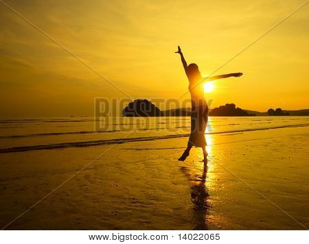 Young woman with raised hands jumping over wet sand