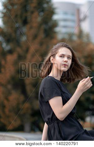 The Girl Smoking A Cigarette.