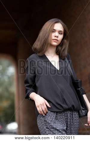The Girl Standing Near A Brick Wall.