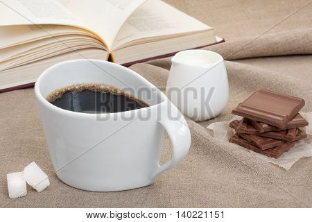 Cup coffee on linen tablecloths with pieces of chocolate sugar and cream against the background an open book.