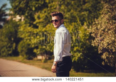 Portrait of stylish handsome young man with bristle standing outdoors. Man wearing shirt and watch.
