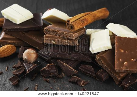 Pieces Of Various Chocolate With Spices On A Dark Background