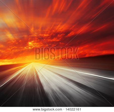 Blurred asphalt road and red clouds
