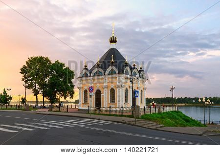 RYBINSK RUSSIA - JULY 21 2016: Unidentified people are near Chapel of Nicholas the Miracle Worker at sunset Rybinsk Russia. Chapel was built in 1867 renovated in 2010-11