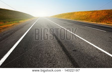 Asphalt road with sunlight on a horizon and clear blue sky