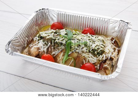 Healthy food and diet concept. Take away of fitness meal. Weight loss nutrition in foil boxes. Vegetable stew with aubergine or eggplant, cherry tomatoes and parmesan cheese at white wood