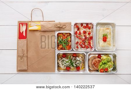 Healthy food delivery, daily meals and snacks. Diet nutrition, vegetables, meat and fruits in foil boxes and brown paper package. Top view, flat lay at white wood with copy space