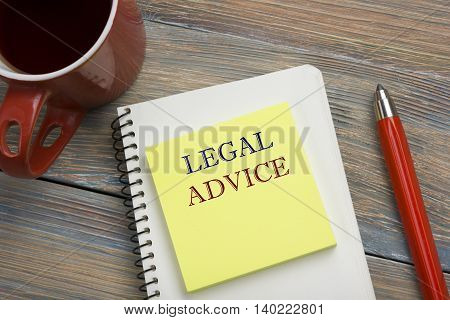 Legal Advice. Notepad with message, coffee cup and red pencil. Office supplies on desk table top view.