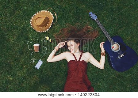 Pretty young girl music lover lying on grass in park, happy and smiling. Female teenager with flat lay composition of paper coffee cup, guitar, hat and mobile phone with earphones. Woman top view
