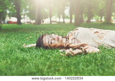 Beautiful young asian girl lying on grass in summer park, happy and smiling. Female korean teenager relax outdoors at sunny day. Attractive pretty woman dreaming, looking up