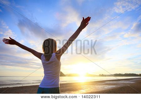 Young woman with raised hands standing on wet sand and looking to a horizon