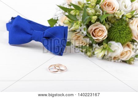 wedding rings and accessories on white wooden table