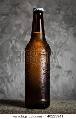 Beer in bottle with ice drops, rustic background