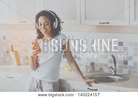 Sunrise. Inspiration words on image of young woman listening music while being home background