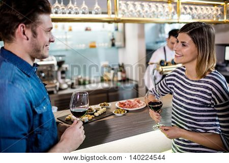 Couple smiling while having wine by bar counter at restaurant