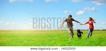Young happy lovers running with a dog on meadow with green grass and blue sky