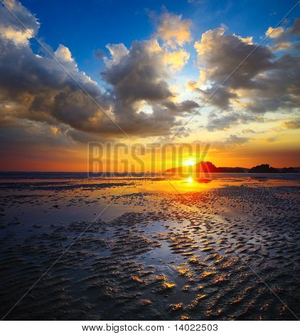 Sunset over beach during tide