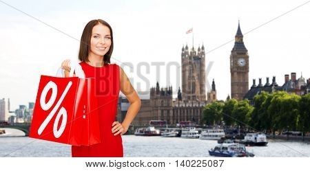 sale, discount, tourism and holidays concept - smiling young woman in red dress with shopping bags with percent sign over london city background