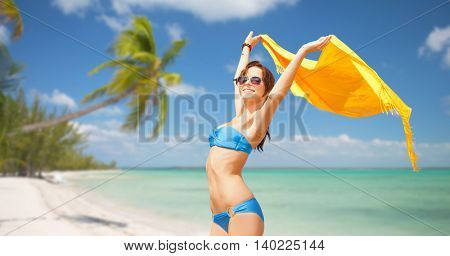 people, summer holidays and vacation concept - beautiful woman in bikini and sunglasses with pareo over exotic tropical beach with palm trees background