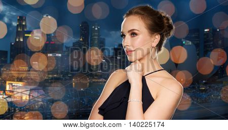 people, luxury, jewelry and fashion concept - beautiful woman in black wearing diamond earrings and bracelet over night singapore city and lights background