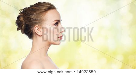 health, people, plastic surgery and beauty concept - beautiful young woman face over yellow holidays lights background