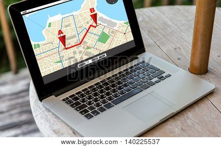 technology, location, navigation, business and modern life concept- close up of open laptop computer with gps navigator map on screen on table at hotel terrace