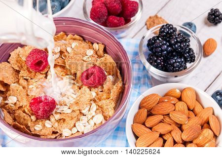 healthy breakfast with cornflakes berries, milk and nuts on wooden table