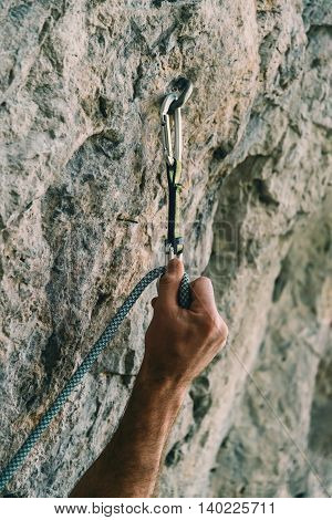 Male climber holding rope and quick-draw on rock wall outdoor. Close-up of hand