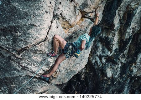 Young woman in safety harness with outfit coating her hand in chalk magnesium on the rock wall outdoor