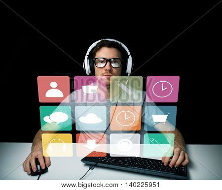 technology, media and people concept - young man or hacker in headset and eyeglasses sitting at table with pc computer keyboard and menu icons on virtual screen