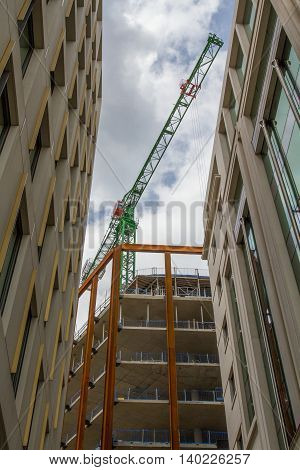 A high rise construction crane towering above tall buildings.