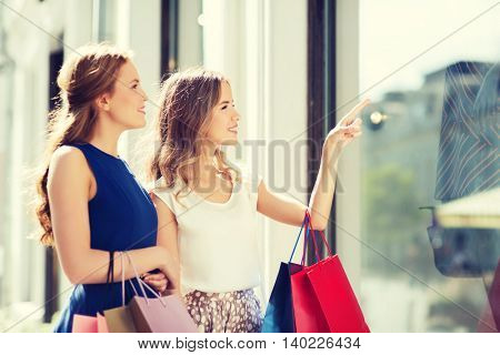 sale, consumerism and people concept - happy young women with shopping bags pointing finger to shop window in city