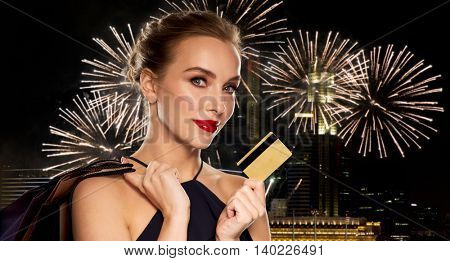 people, luxury and sale concept - beautiful woman with credit card and shopping bags over night singapore city and firework background