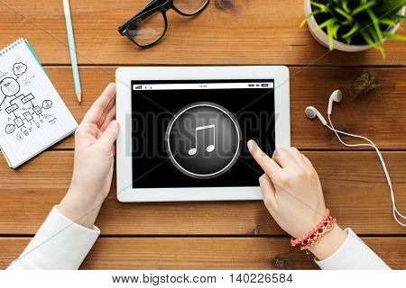 technology, people and multimedia concept - close up of woman with music media player icon on tablet pc computer screen on wooden table