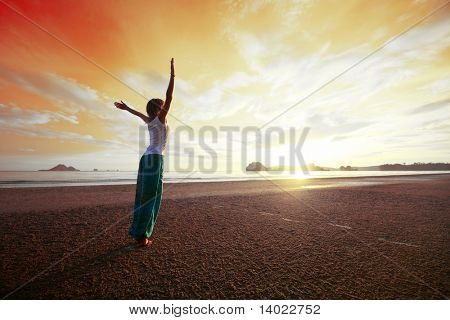 Young woman with raised hands standing on wet sand and looking to a red sky