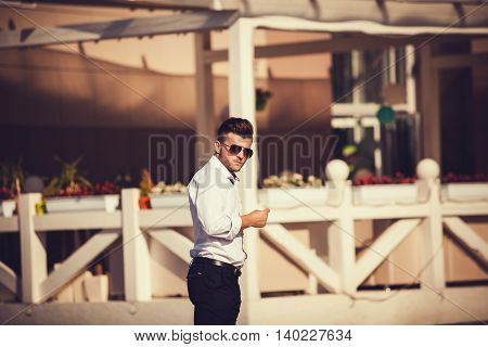 Elegant young handsome man in shirt outdoors