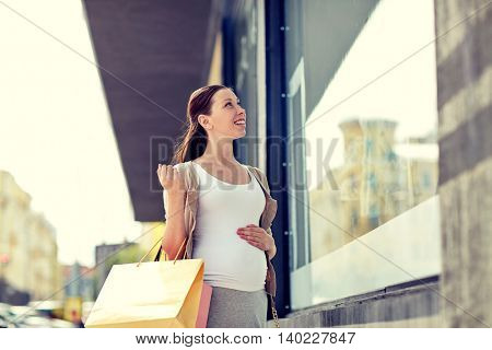 pregnancy, motherhood, people and expectation concept - happy smiling pregnant woman with shopping bags at city street