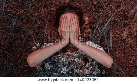Pretty brunette woman covering her face with both hands