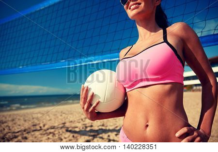 summer vacation, sport and people concept - close up of young woman with volleyball ball and net on beach